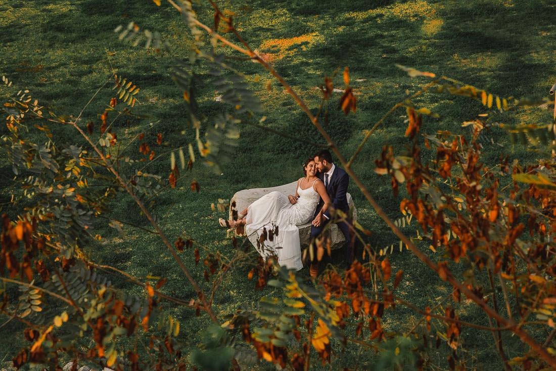 novios abrazados, novios en sesion de fotos, pareja en la naturaleza, novios comiendo, cerro, arbol, flores, hojas, sombras, troncos, contraluz, sesion de fotos, post wedding, recien casados