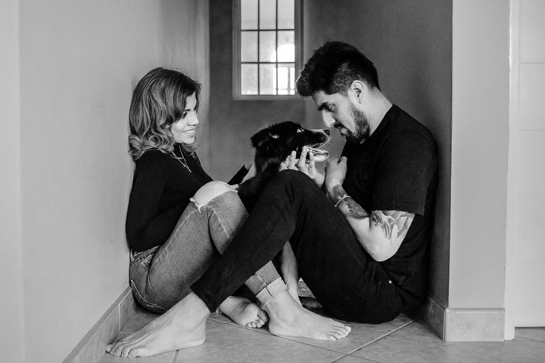 pareja de novios posando para foto en casa, contraluz, sesion con mascota, composicion de fotografia, personas riendo, sesion de fotos alegre y divertida