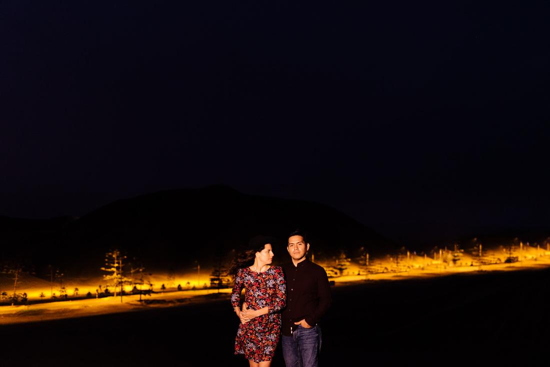 pareja de novios posando para la foto, escena dramatica, luz artificial de noche, carrereta de fondo